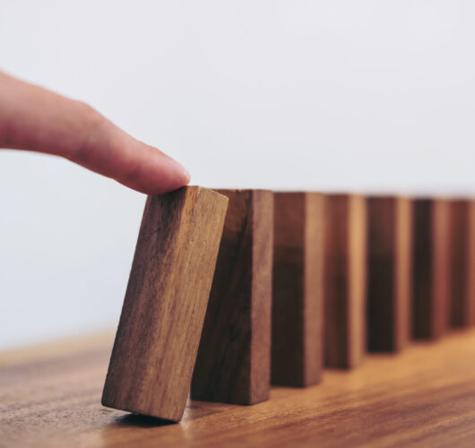 Risk and strategy in business, Close up of businessman hand gambling starting push wooden block on a line of domino.